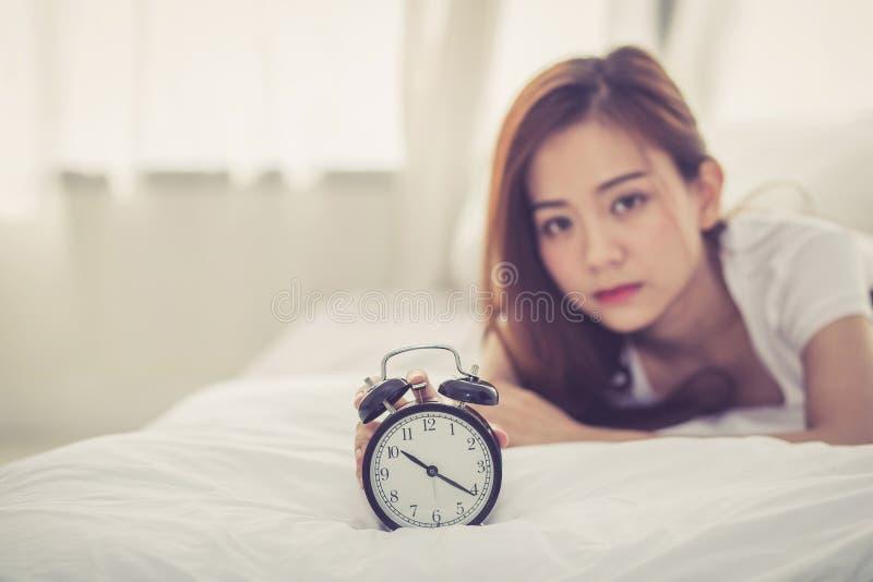 Schöne asiatische junge Frau stellen Wecker am guten Morgen ab, stockfotos