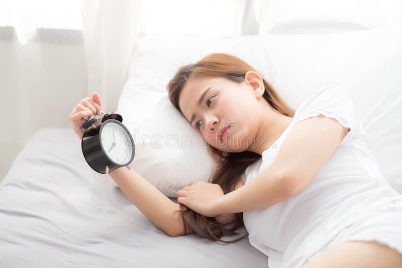 Schöne asiatische junge Frau stellen Wecker am guten Morgen, aufwachen für Schlaf mit Nahaufnahmevordergrundwecker ab stockfoto