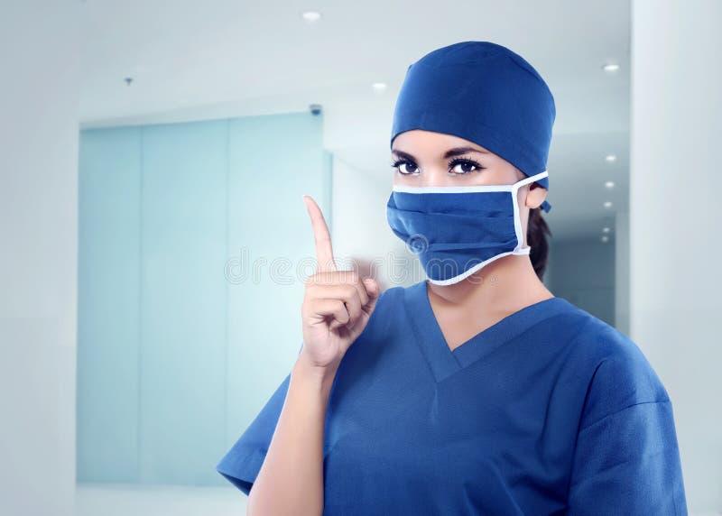 Schöne asiatische Krankenschwester mit medizinischer Maske ihre Hand zeigend stockfoto