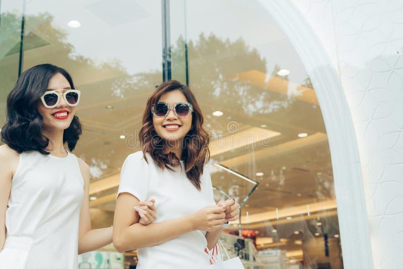 Schöne asiatische Mädchen mit Einkaufstaschen gehend auf Straße stockbilder
