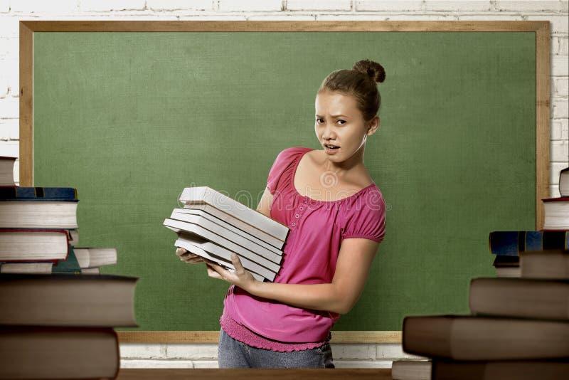 Schöne asiatische Studentfrau mit Buchstellung stockfotos