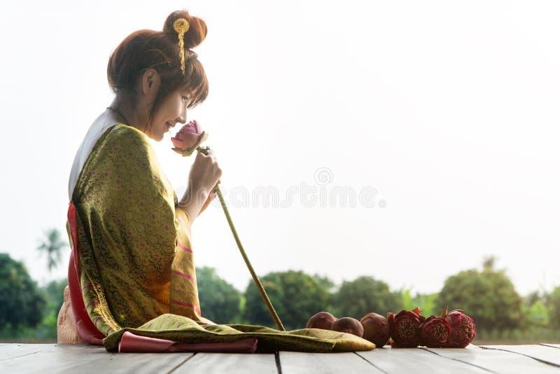 Schöne Asien-Frauen, die traditionelles thailändisches Kleid tragen und auf Bretterboden sitzen Ihre Hände hält Lotosblumen- und  lizenzfreie stockbilder