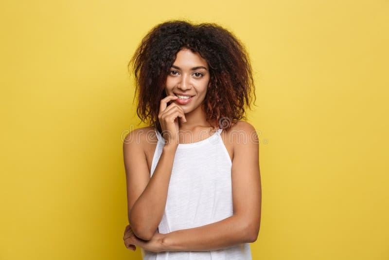 Schöne attraktive Afroamerikanerfrau mit dem gelockten Afrohaar denkend an etwas Gelber Studiohintergrund exemplar lizenzfreie stockfotos