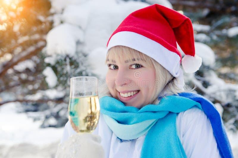Schöne attraktive Blondine in einem roten Weihnachtshut mit einem Glas Champagner in ihrer Hand lizenzfreie stockfotos