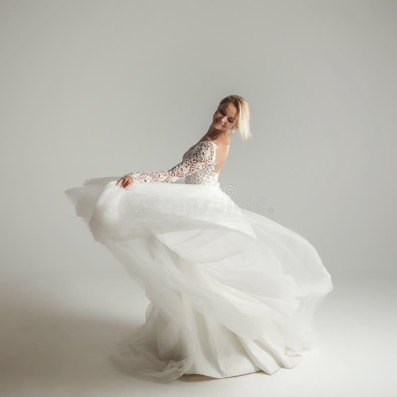 Schöne attraktive Braut im Hochzeitskleid mit langem Tellerrock, weißem Hintergrund, Tanz und Lächeln lizenzfreies stockbild