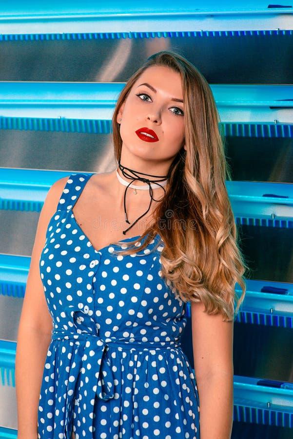 Schöne attraktive recht langhaarige junge Frau im blauen Kleid des Tupfens und in den Strümpfen und in den roten Schuhen im Stift lizenzfreie stockfotos