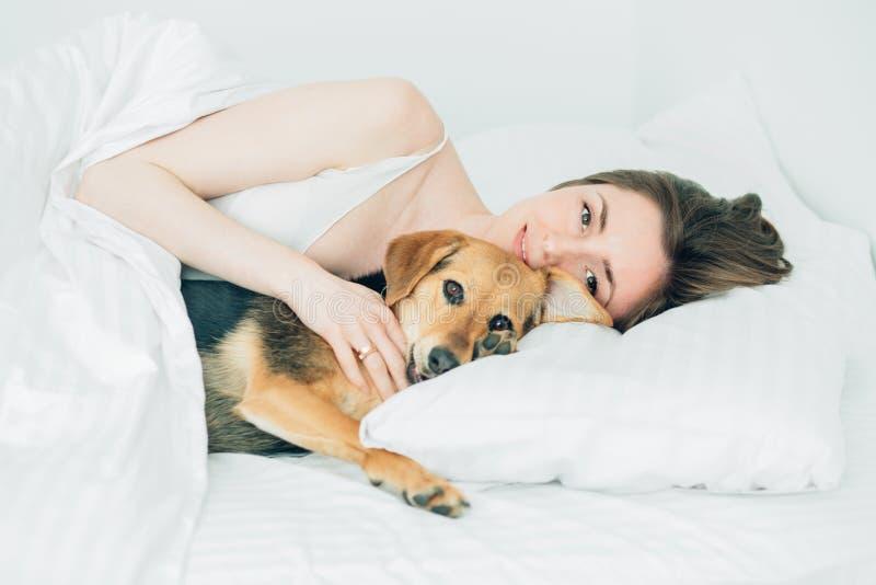 Schöne aufgeregte junge Frau und ihr netter Kanaillehund sind täuschen herum und betrachten Kamera beim Lügen, das mit einer Deck stockfotografie