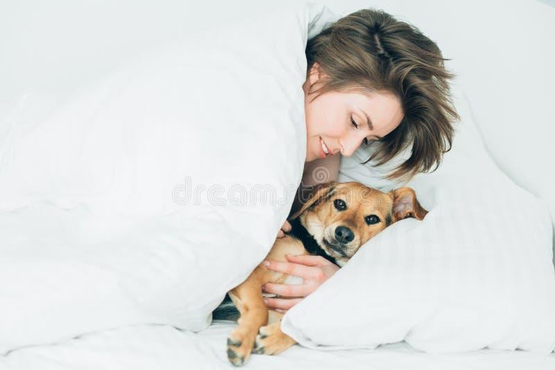 Schöne aufgeregte junge Frau und ihr netter Kanaillehund sind täuschen herum und betrachten Kamera beim Lügen, das mit einer Deck lizenzfreie stockbilder