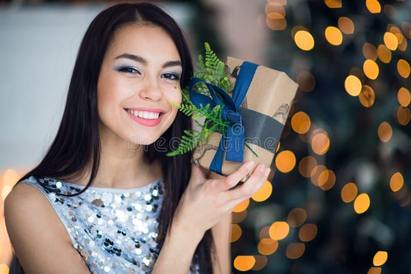 Schöne aufgeregte lächelnde junge Frau mit dem anwesenden Geschenk, das glücklichem nahem Weihnachtsbaum glaubt Glückliches junge lizenzfreie stockfotos