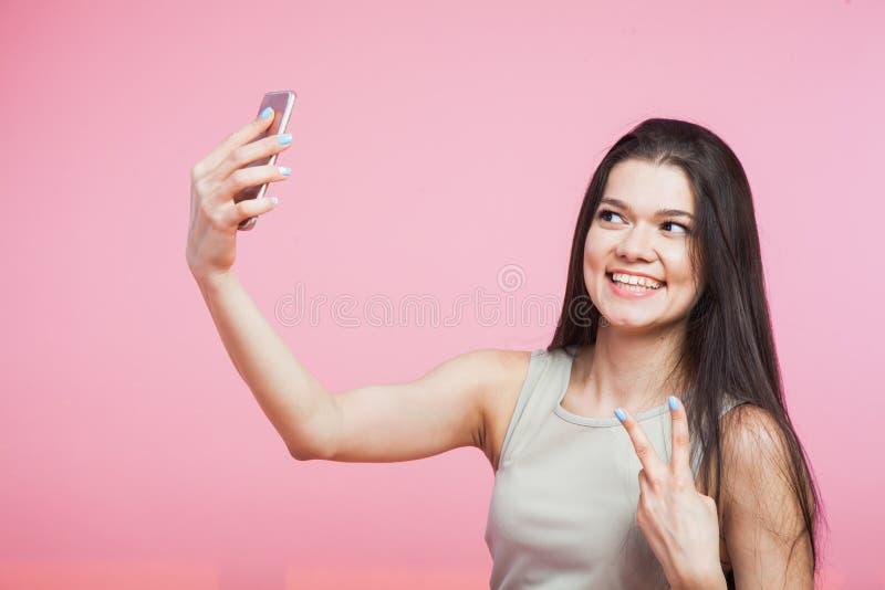 Schöne ausdrucksvolle Frau, die selfie auf Smartphone macht lizenzfreie stockfotos