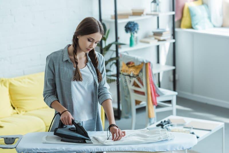 schöne bügelnde weiße Hosen der jungen Frau lizenzfreie stockbilder