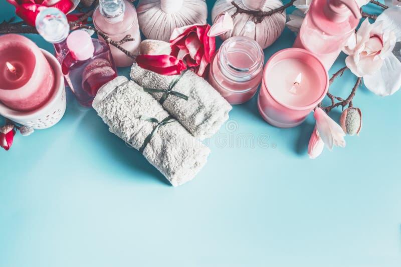 Schöne Badekurorteinstellung mit Tüchern, Blumen, Kerzen und Körperpflegekosmetik am hellblauen Hintergrund, Draufsicht mit Kopie stockfoto
