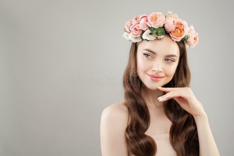 Schöne Badekurortfrau, die beiseite schaut Perfektes Modell mit klarer Haut, dem langen braunen Haar und den Blumen stockfoto