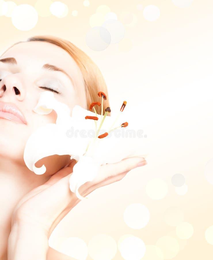 Schöne Badekurortfrau mit lilly lizenzfreies stockfoto