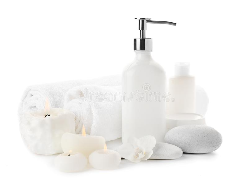 Schöne Badekurortzusammensetzung mit Kosmetik, Massagesteinen und brennenden Kerzen auf weißem Hintergrund lizenzfreie stockbilder