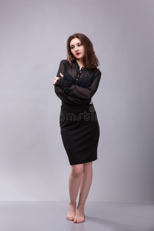 Schöne barfüßigbrunettefrau kleidete in der schwarzen Kleidung am grauen Hintergrund an lizenzfreie stockfotos