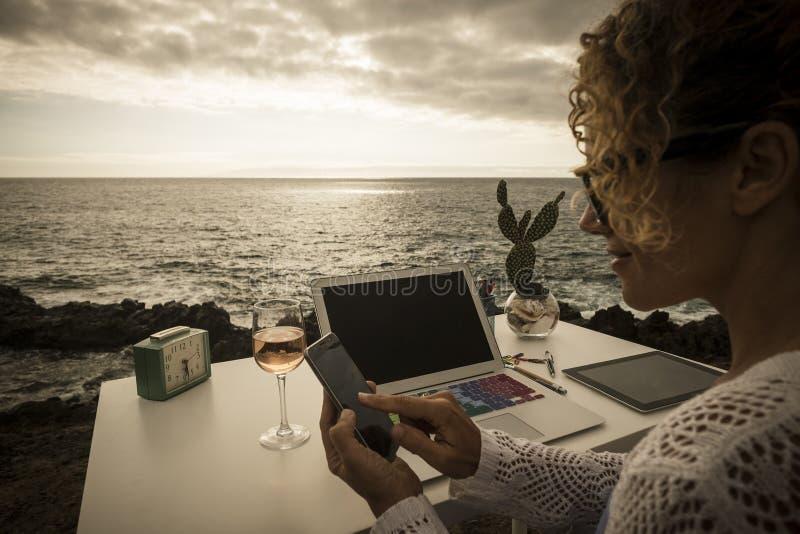 Schöne behilfliche Berufsdame bei der Arbeit im alternativen Freiheitskonzeptbüro vor dem Ozean genießen Sie ein unterschiedliche lizenzfreies stockbild