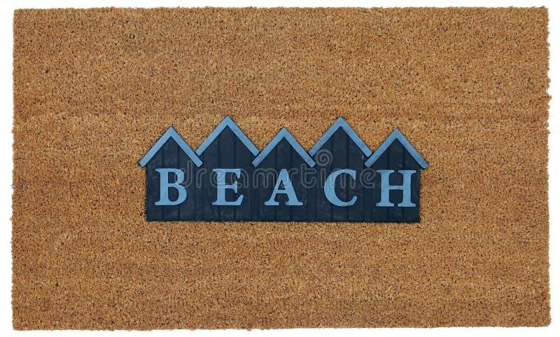 Schöne beige und blaue zute/Coir Türmatte im Freien mit STRAND-Text in der Gebirgsart stockbilder