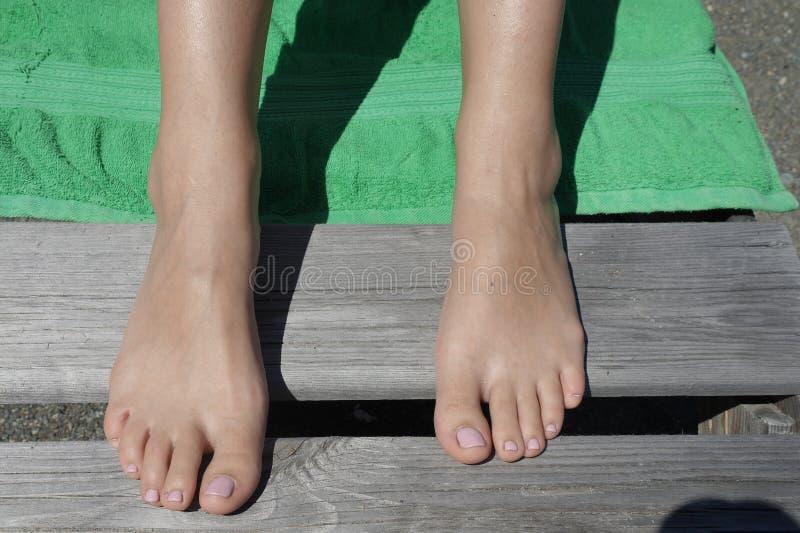 Schöne Beine von Touristen auf dem Strand stockbild