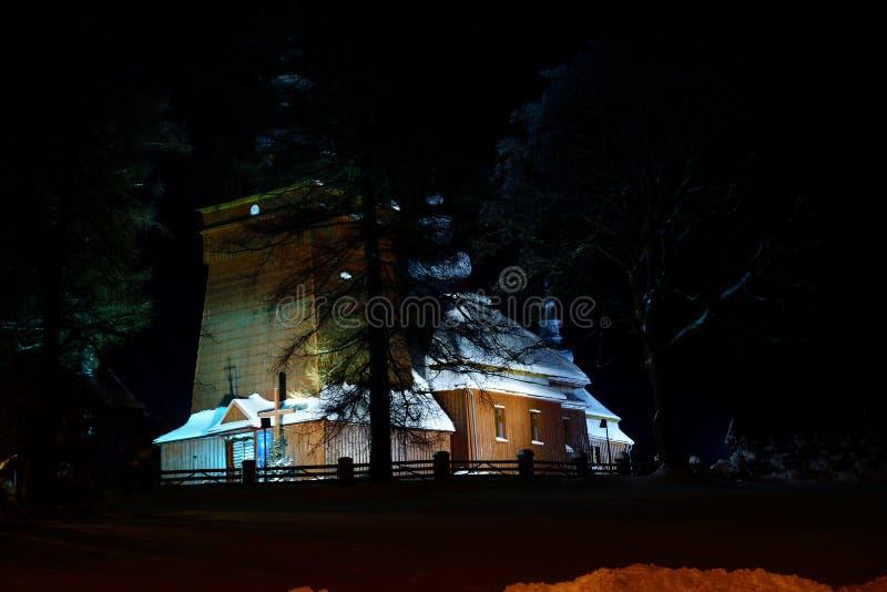 Schöne belichtete hölzerne Kirchenphotographie im Nachtwinter voll des Schnees Tylicz Polen stockfotos
