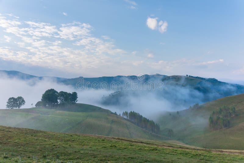Schöne Berglandschaft eines nebeligen Morgens mit und alten des Hauses, der Bäume und der Wolken lizenzfreie stockbilder