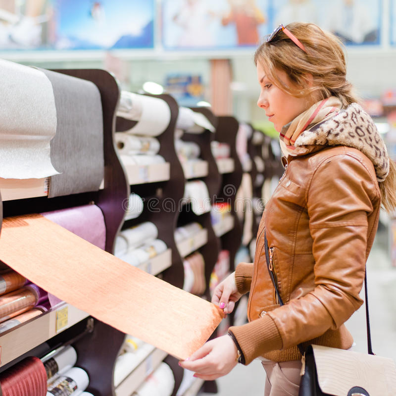 Schöne beschäftigte Frau im DIY-Supermarkt, der Tapetenporträtbild wählt lizenzfreie stockfotografie