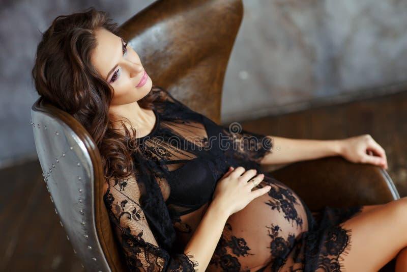Schöne, bezaubernde und sexy schwangere Frau in schwarzem Fischnetzdr. lizenzfreies stockfoto