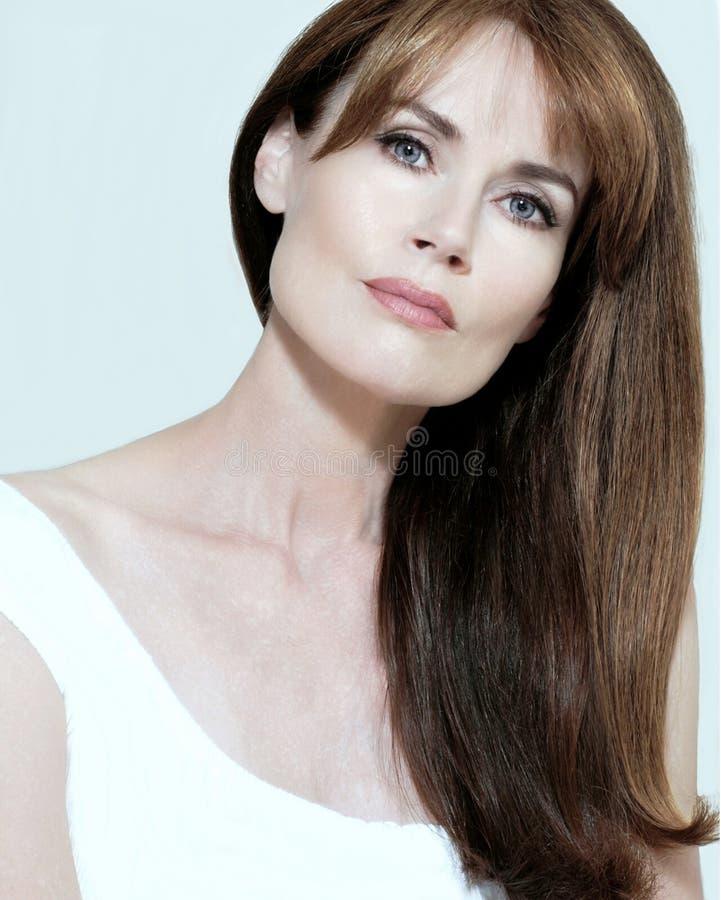 Schöne blauäugige Frau mit dem langen, geraden Haar stockfoto