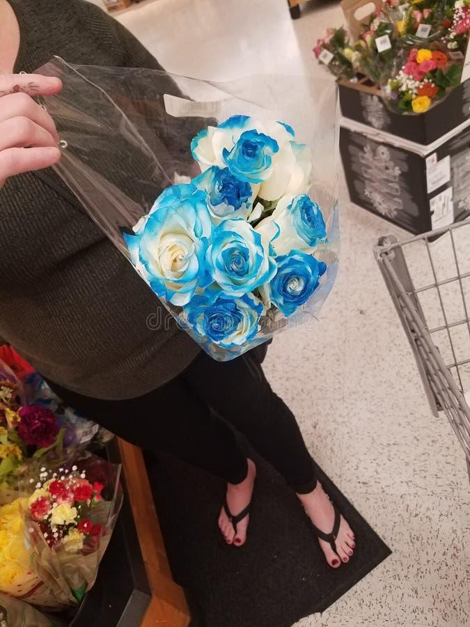 Schöne blaue Blumen und ein Weibchen in Sandalen stockfotografie