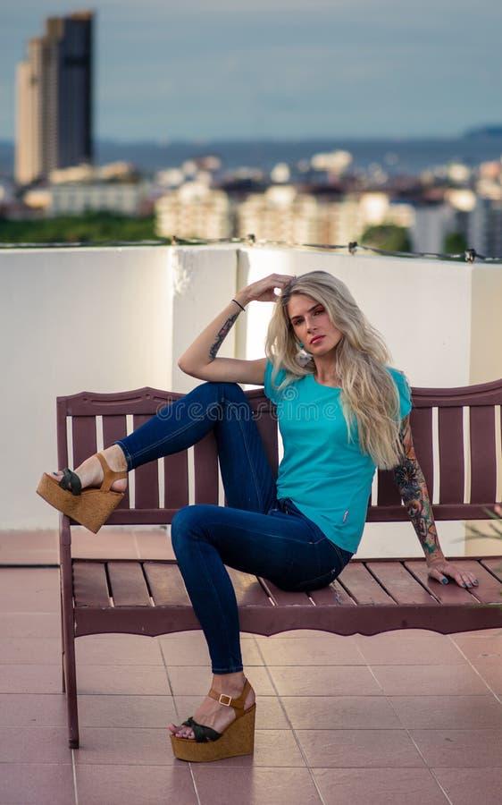 Schöne blonde Aufstellung für die Kamera, die auf einer Holzbank auf dem Dach sitzt Trägt Jeans und Schuhe auf einem Hochbahnstei stockfotografie