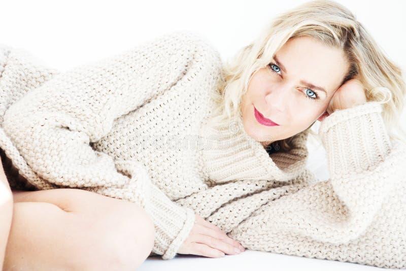 Schöne blonde Frau in der beige Strickjacke, die im Bett liegt stockfotografie
