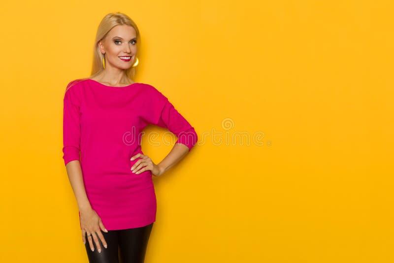 Schöne blonde Frau in der rosa Strickjacke wirft mit der Hand auf Hüfte auf, lächelt und betrachtet Kamera lizenzfreie stockfotos