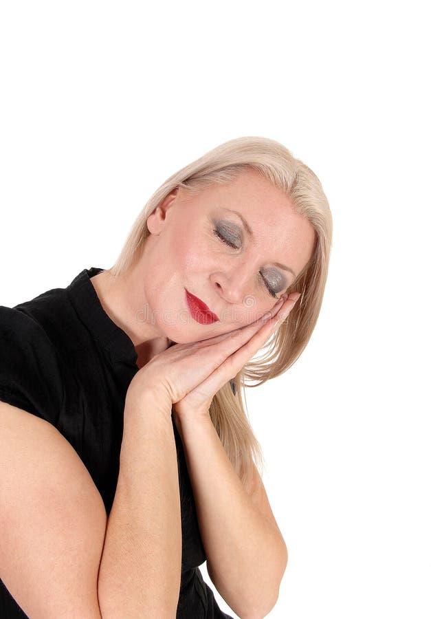 Schöne blonde Frau, die auf ihren Händen schläft stockfotos