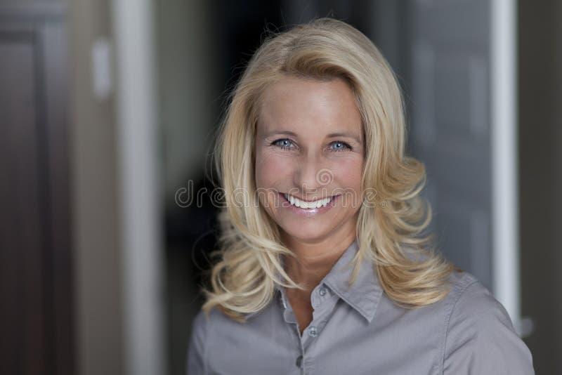 Schöne blonde Frau, die an der Kamera lächelt lizenzfreies stockfoto