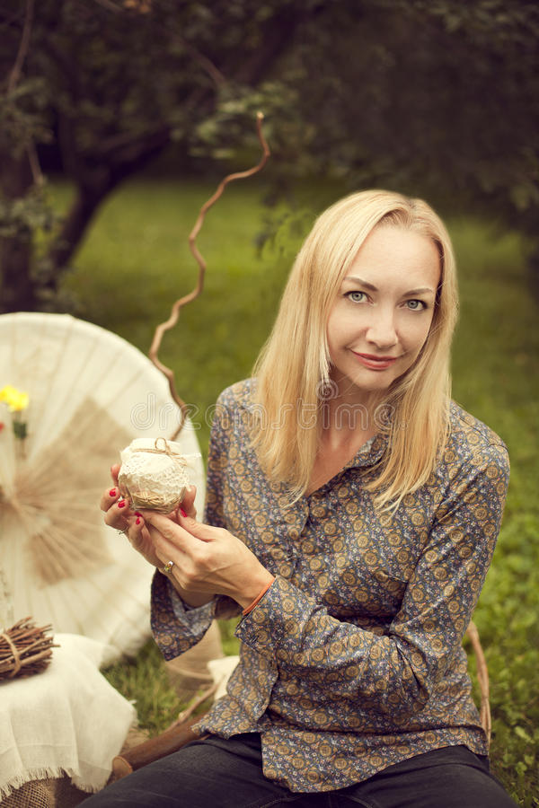 Schöne blonde Frau, die draußen lächeln sitzt Der Florist, ein De lizenzfreie stockfotos