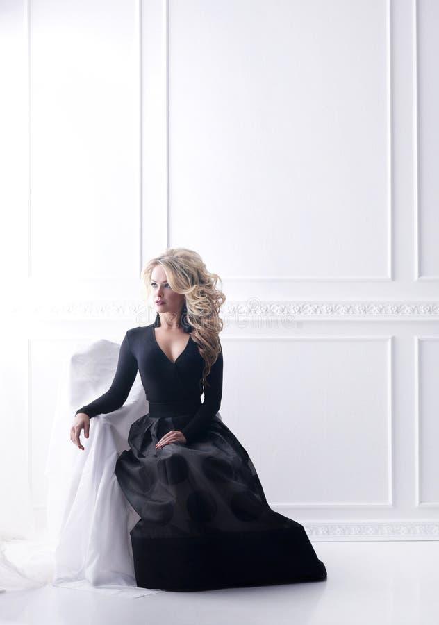 Schöne blonde Frau, die in einem schwarzen Kleid aufwirft Mädchen, das auf Lehnsessel im Retro- Innenraum sitzt lizenzfreie stockfotos