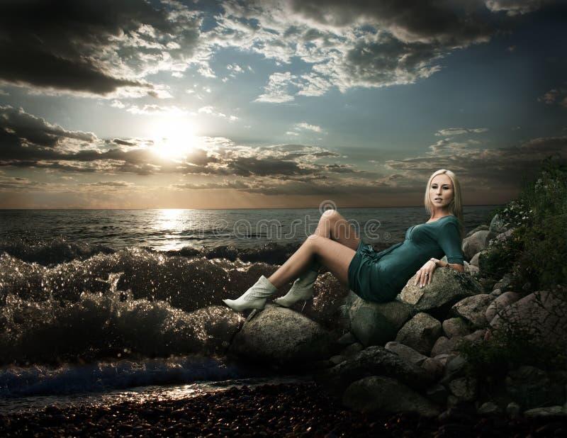 Schöne blonde Frau, die nahe dem Meer sitzt stockfotos
