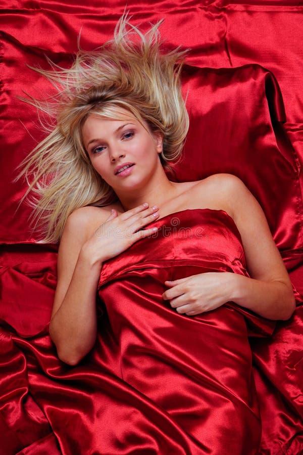 Schöne blonde Frau in einem Bett der roten silk Blätter lizenzfreie stockfotografie
