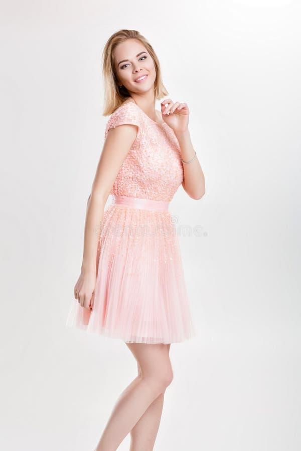 Schöne blonde Frau in einem rosa Cocktailkleid Tanzen und einem havin lizenzfreie stockfotografie