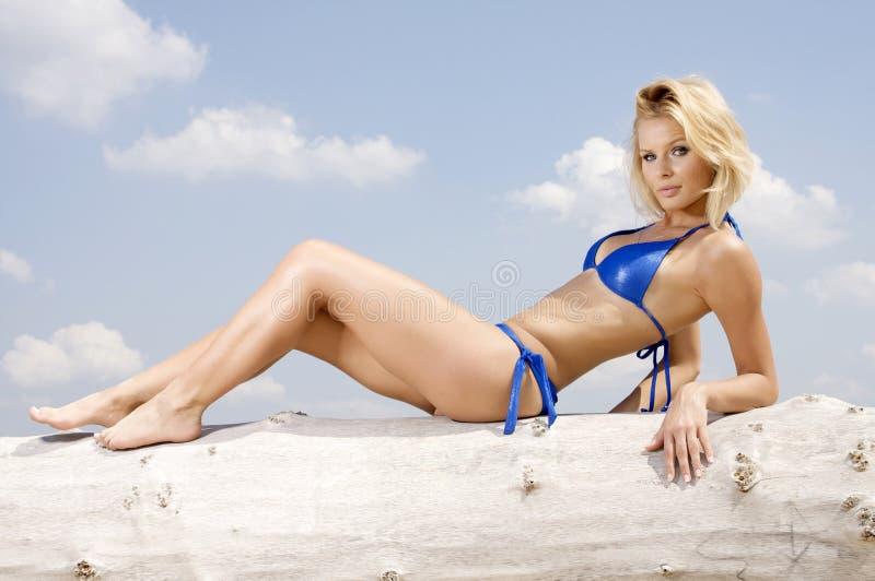 Schöne blonde Frau im blauen Bikini stockbilder