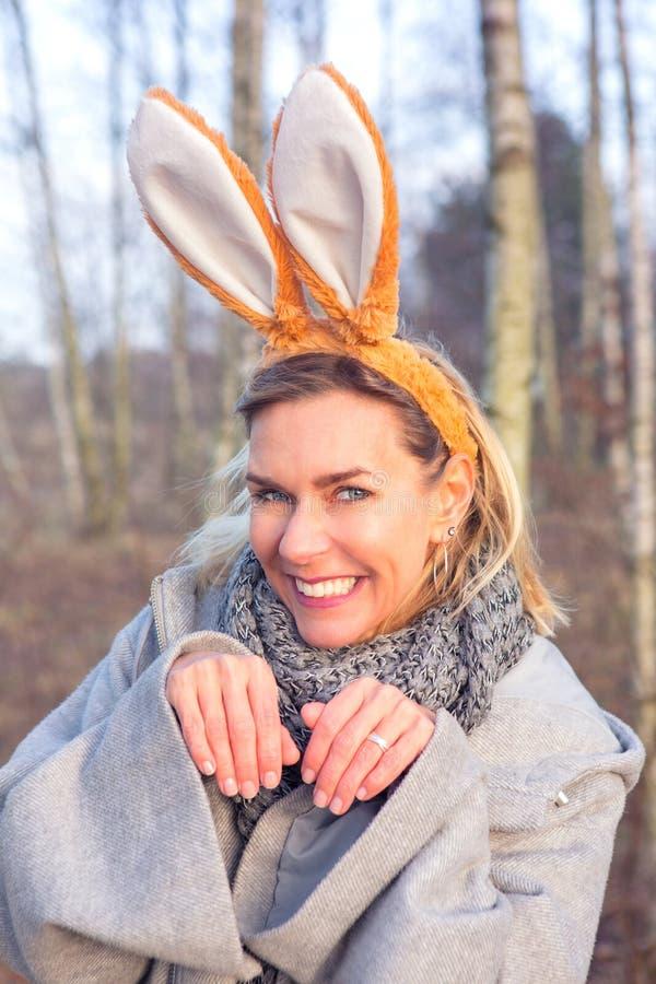 Schöne blonde Frau im Park mit den Häschenohren stockfotografie