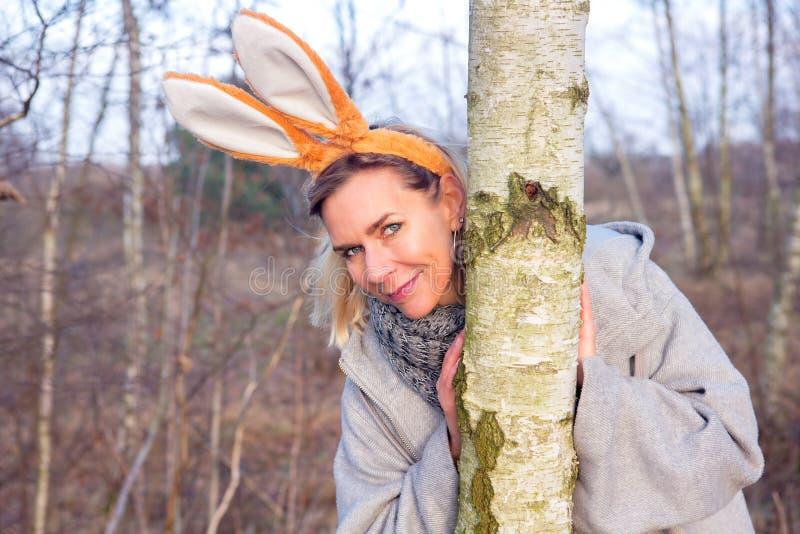 Schöne blonde Frau im Park mit den Häschenohren lizenzfreies stockbild