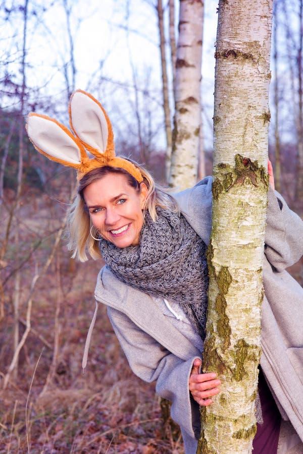 Schöne blonde Frau im Park mit den Häschenohren stockfotos