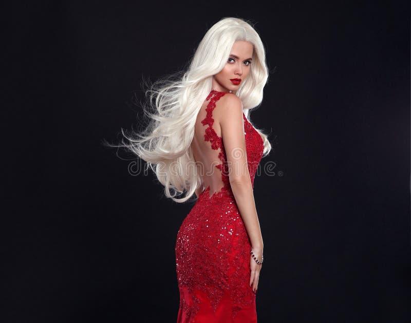 Schöne blonde Frau im roten Kleid lokalisiert auf schwarzem Hintergrund stockbilder