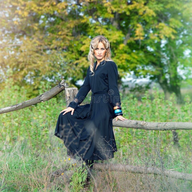 Schöne blonde Frau im schwarzen Kleid lizenzfreie stockfotografie