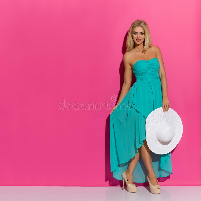 Schöne blonde Frau im Türkis-Kleid und den hohen Absätzen hält weißen Sun-Hut und schaut weg stockbilder