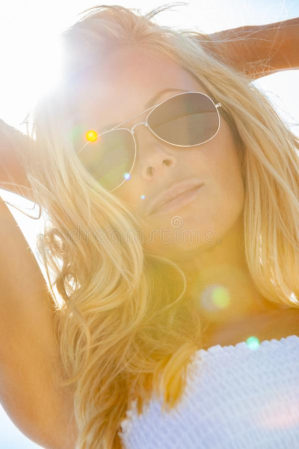 Schöne blonde Frau im weißen Kleid und in der Sonnenbrille am Strand lizenzfreie stockfotografie