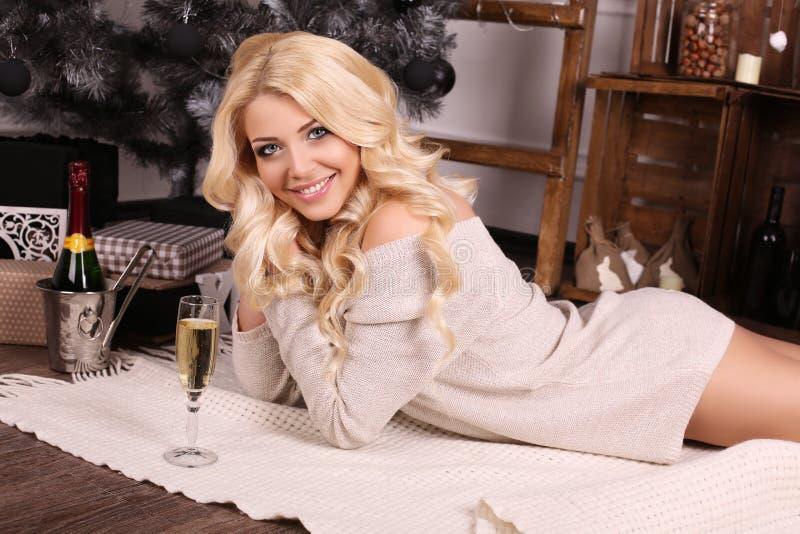 Schöne blonde Frau mit dem Champagner, der neben Weihnachtsbaum aufwirft lizenzfreies stockfoto