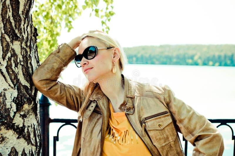 Schöne blonde Frau mit dem langen Haar in der Sonnenbrille, die nahe dem Baum aufwirft r lizenzfreie stockbilder