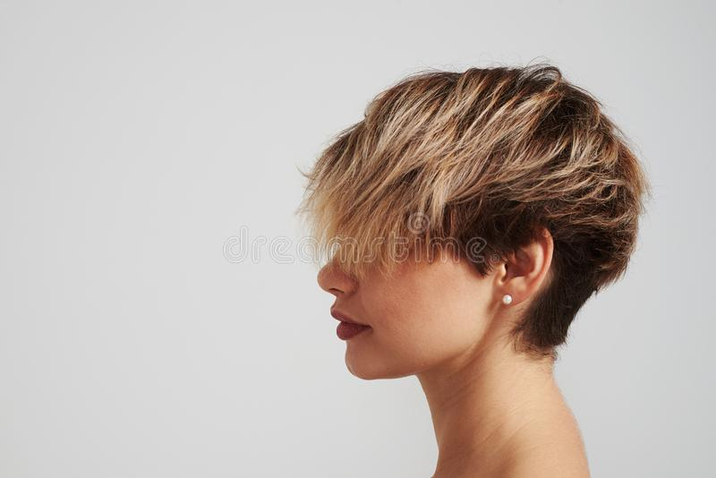Schöne blonde Frau mit der Kurzhaarfrisur, die am Studio aufwirft stockfoto